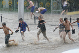 Teenagers Playing In Floodwaters Photographic Print by Ria Novosti