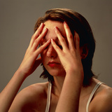 Meditating Young Woman's Face with Hands on Eyes Photographic Print by Damien Lovegrove