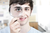 Teenage Boy with Magnifying Glass Photographic Print by Science Photo Library