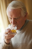 Senior Man Drinking Whiskey Photographic Print by Science Photo Library