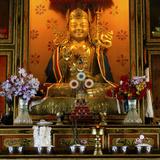 Golden Statue of a Seated Buddha Surrounded by Flowers Photographic Print