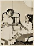 Orang Ulu Nurse Attending an Orang Ulu Patient in a Hospital in Sibu, Sarawak, Malaysia C.1950 Photographic Print