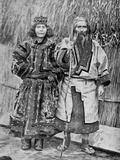 Ainu Couple Outside the Traditional Ainu Home of a Reed Thatched Hut, Late 19th Century Photographic Print by  Kajima and Suwo