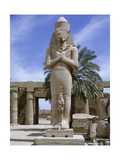 A Colossal Statue of Ramesses II with a Princess, Perhaps His Daughter Bentanta, Standing Between… Giclee Print
