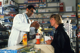 Pharmacist with Customer Prints by Geoff Tompkinson