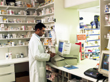 Pharmacist Using a Computer In a Pharmacy Photo by Geoff Tompkinson