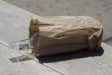Discarded Rum Bottle In Paper Bag Photographic Print by Mark Williamson