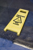 Wet Floor Sign In Puddle Photographic Print by Mark Williamson