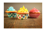 Three Different Colors Cupcakes On A Wooden Table, Blue, Yellow And Pink Print by pink candy