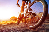 Low Angle View Of Cyclist Riding Mountain Bike On Rocky Trail At Sunrise Posters by  warrengoldswain