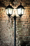 Detail Of Street Lamp With Brick Wall Background Photographic Print by  MartinM303
