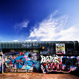 A Building Covered In Graffiti And A Beautiful Sky Above Prints by  sammyc