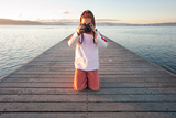 Little Girl Taking A Photograph On A Pier Photographic Print by  xavigm
