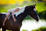 Child Sits On A Horse In Meadow Near Small River Photographic Print by Alexia Khruscheva