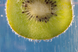 A Slice of Kiwi Fruit in a Glass of Sparkling Mineral Water Photographic Print by Brian Jannsen