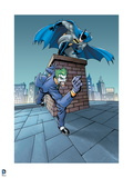 Batman: Batman Crouching on a Chimney About to Jump with The Joker Running on Rooftop Below Him Print