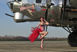 Beautiful 1940's Style Pin-Up Girl Standing in Front of a B-17 Bomber Fotografiskt tryck