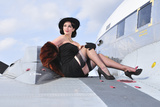 Glamorous Woman in 1940's Style Attire Sitting on a Vintage Aircraft Fotografická reprodukce