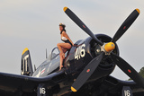 1940's Style Navy Pin-Up Girl Sitting on a Vintage Corsair Fighter Plane Fotografická reprodukce