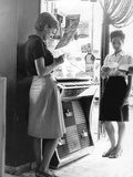 Two Girls Reading Next to a Jukebox Photographic Print