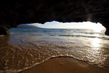 The Lip of a Foamy Wave Laps a Sandy Beach Inside an Ocean Cave Photographic Print by Jason Edwards