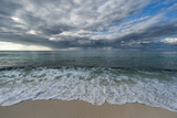 Indian Ocean Surf Surging onto a Sandy Beach, under a Dramatic Cloud-Filled Sky Fotografisk tryk af Sergio Pitamitz