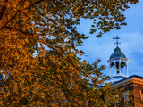 The Cupola Atop Bates College Framed by Tree Branches Bearing Autumn-Hued Leaves Photographic Print by Babak Tafreshi