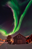 The Aurora Borealis, or Northern Lights, Appear Above a Village Fotografisk tryk af Babak Tafreshi