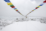 A Porter Walks by a Puja with Prayer Flag in Everest Base Camp, Nepal Photographic Print by Alex Treadway