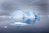 A Blue Iceberg under Cloud-Filled Skies, in Glassy Calm Water Photographic Print by Ira Meyer