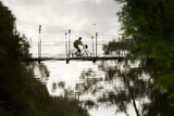 Reflection of a Mountain Biker on a Munda Biddi Trail Suspension Bridge, Collie River, Australia Photographic Print by Bill Hatcher