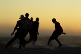 Silhouetted Men Playing Soccer at Sunset Photographic Print by Beverly Joubert