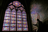 A Stained Glass Window, Statue, and Mural in Notre Dame Cathedral Photographic Print by Babak Tafreshi
