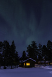 The Northern Lights or Aurora Borealis over Warmly-Lit Cottages and Silhouetted Evergreen Trees Photographic Print by Jonathan Irish