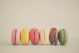 A Rainbow Selection of Sweet French Macarons Sitting in a Row. Fotodruck von Laura Evans