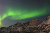 The Northern Lights, or Aurora Borealis, Dance over Rugged Mountains Photographic Print by Babak Tafreshi