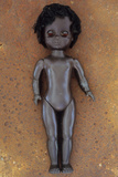Modern Plastic Black Girl Doll Slightly Scratched and Soiled Lying on Rusty Metal Sheet Photographic Print by Den Reader
