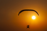 Silhouette of a Microlight and Passenger in Flight at Sunset Photographic Print by Beverly Joubert