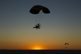 Silhouettes of Two Microlights and Passengers in Flight at Sunset Photographic Print by Beverly Joubert