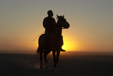 A Silhouetted Man on Horseback at Sunset Photographic Print by Beverly Joubert