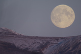 A Full Moon Rising over Snow-Dusted Mountains Photographic Print by Michael S. Quinton