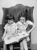 1920s-1930s Two Girls Sitting Side by Side in Chair Reading Book Photographic Print