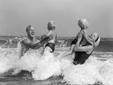 1960s-1970s Family Father Mother Holding Up a Twin Sons in the Ocean Surf Photographic Print