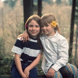 Two Young Girls with Flowers in their Hair Sitting Outside Retro 1970s Photographic Print