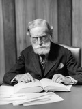 1930s Elder Man in Glasses Sitting at Desk Reading Book Photographic Print