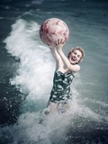 1950s Woman Jumping in Surf Holding Up Beach Ball Photographic Print