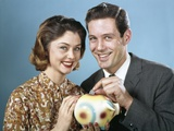 1950s-1960s Young Couple Man and Woman Put Quarter in Savings Piggy Bank Photographic Print