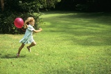 1980s Little Girl with a Red Balloon Running in the Grass Photographic Print