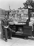 1940s Boy Sitting at Corner Newsstand Writing in Notepad Photographic Print