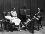 1930s Family of Four in Living Room Gathered around Listening to Radio Photographic Print